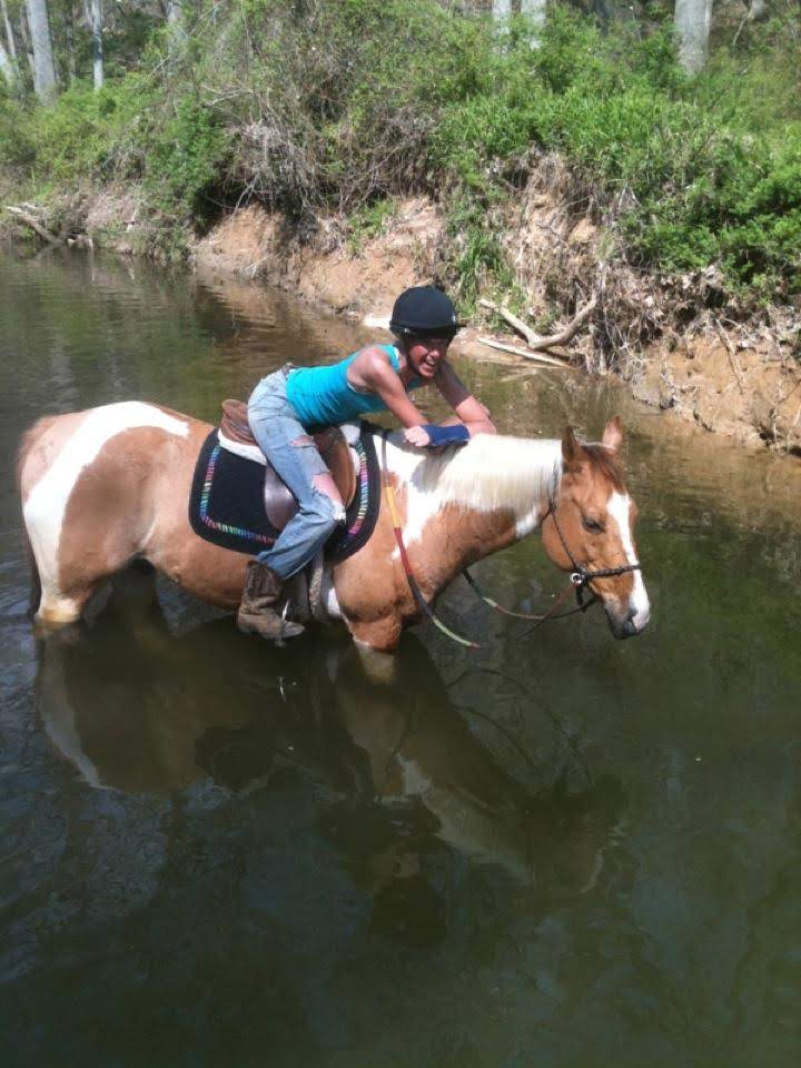 Ellison Hartley on a paint horse standing in a river